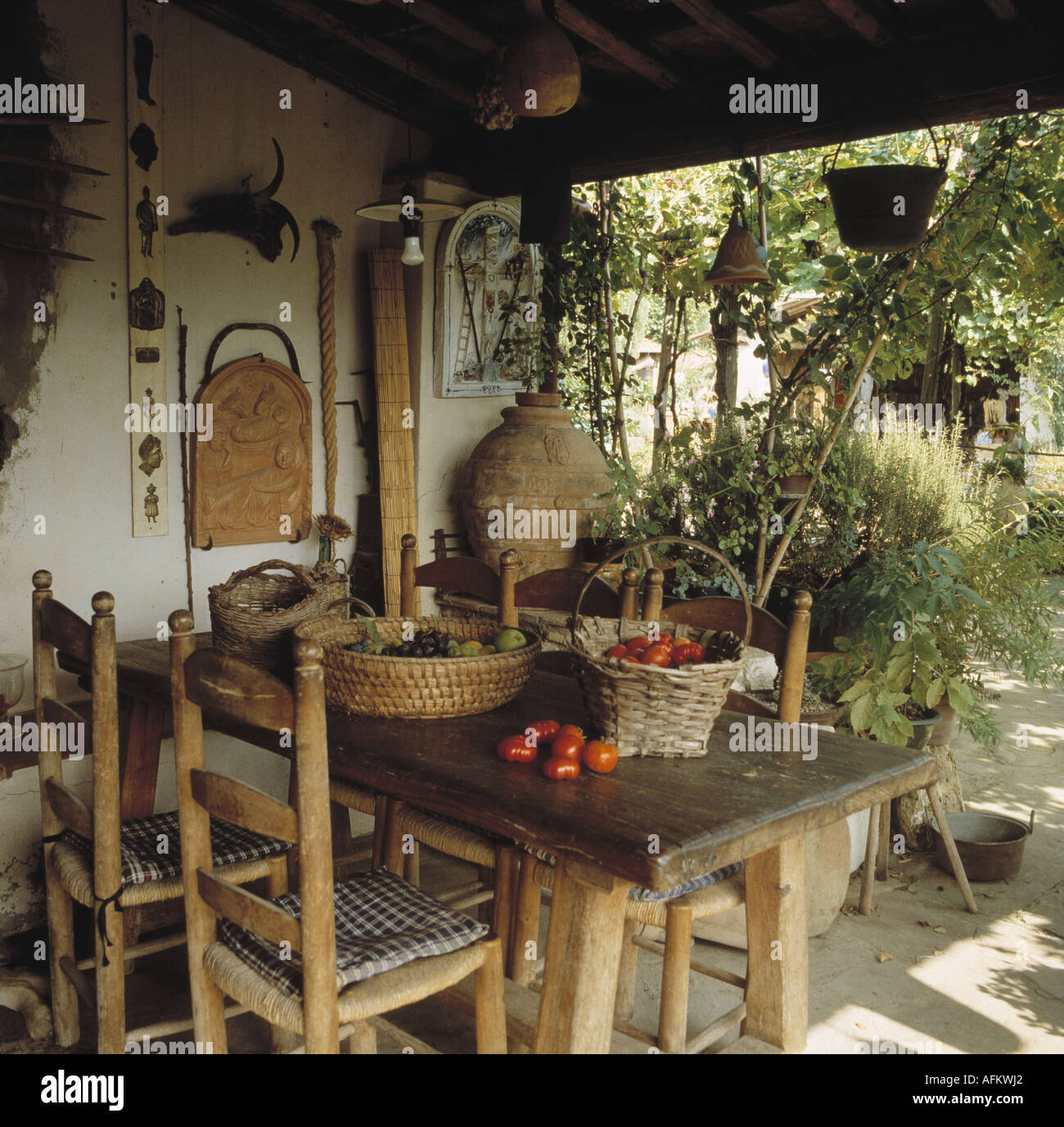 Rustic wooden table and ladder-back chairs on veranda of small Stock ...