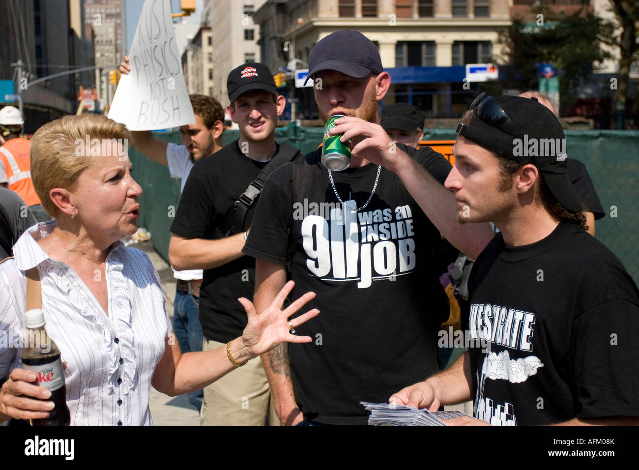 9/11 conspiracy theorists (center and right) argue with a passerby (left) about what really happened to the World - Stock Image