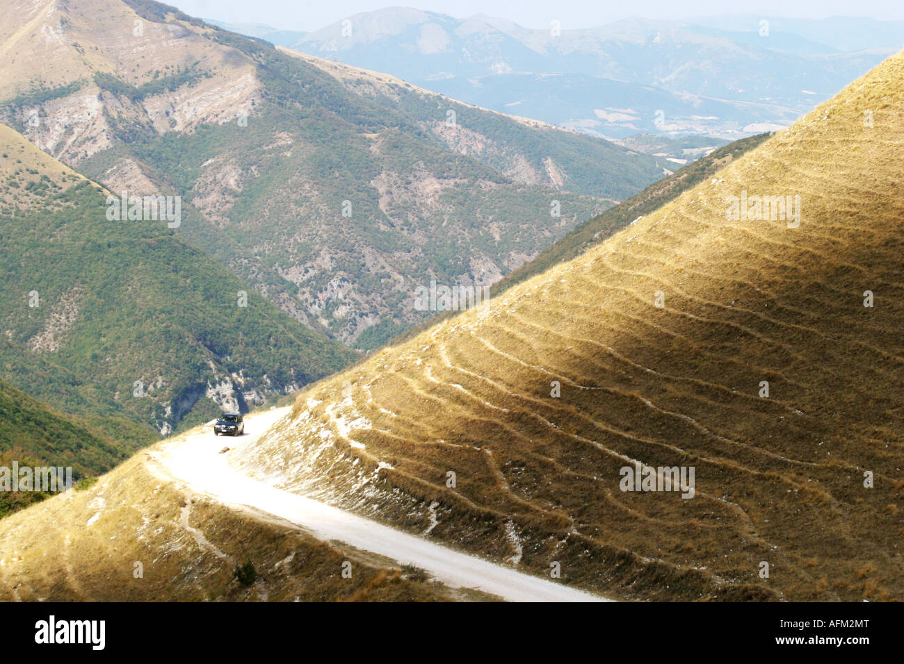 """access road """"strada bianca"""" curves around the  Sasso Tetto  mountain at Pintura  in the Sibillini National Park Stock Photo"""