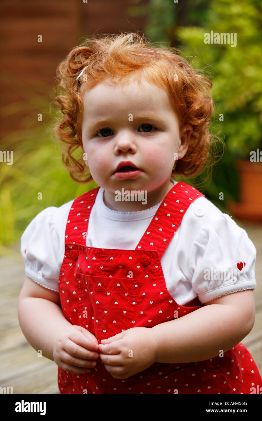 Little girl with red hair in red clothes looking to camera
