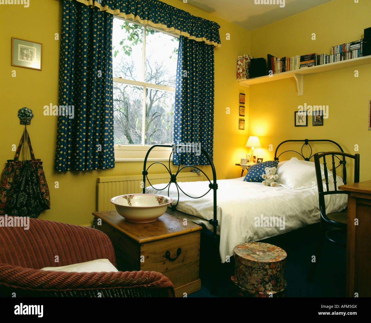 Shelf Above Single Wrought Iron Bed In Yellow Bedroom With Spotted Stock Photo Alamy
