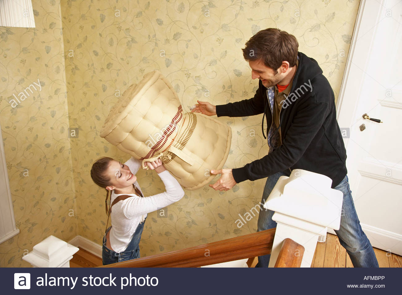 High angle view of a young woman giving a rolled up mattress to a young man - Stock Image