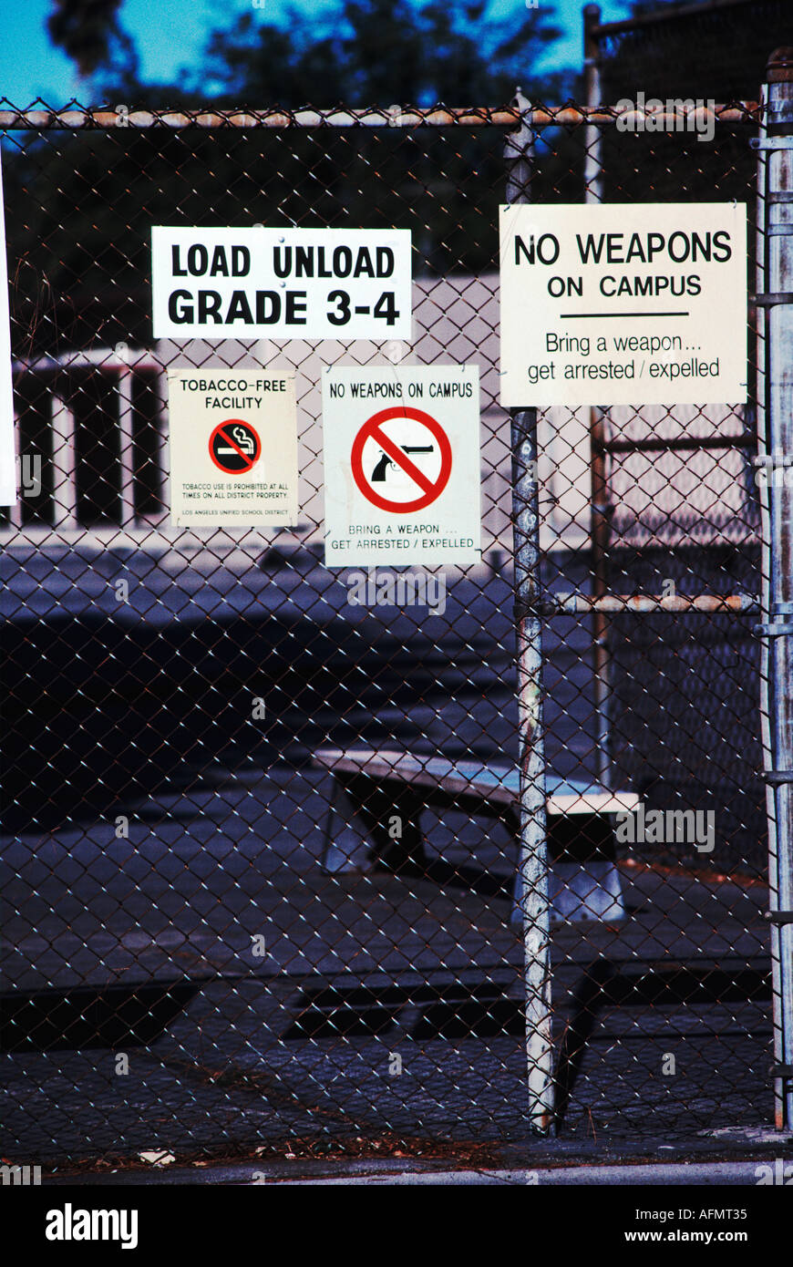 No weapons smoking warning signs on fence around a Los Angeles Unified School District public school California USA - Stock Image