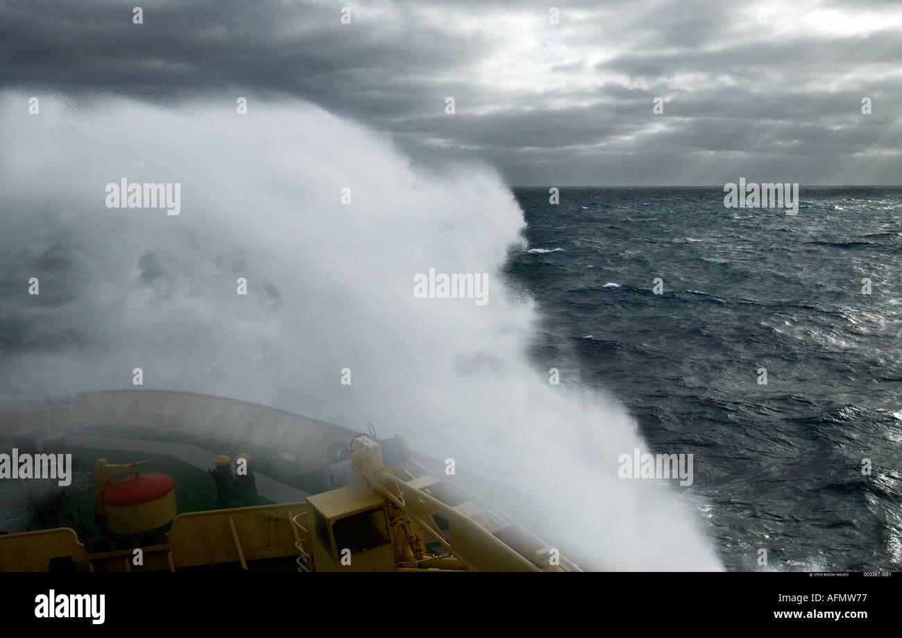 Ice breaker crashing through stormy seas Antartica Stock Photo