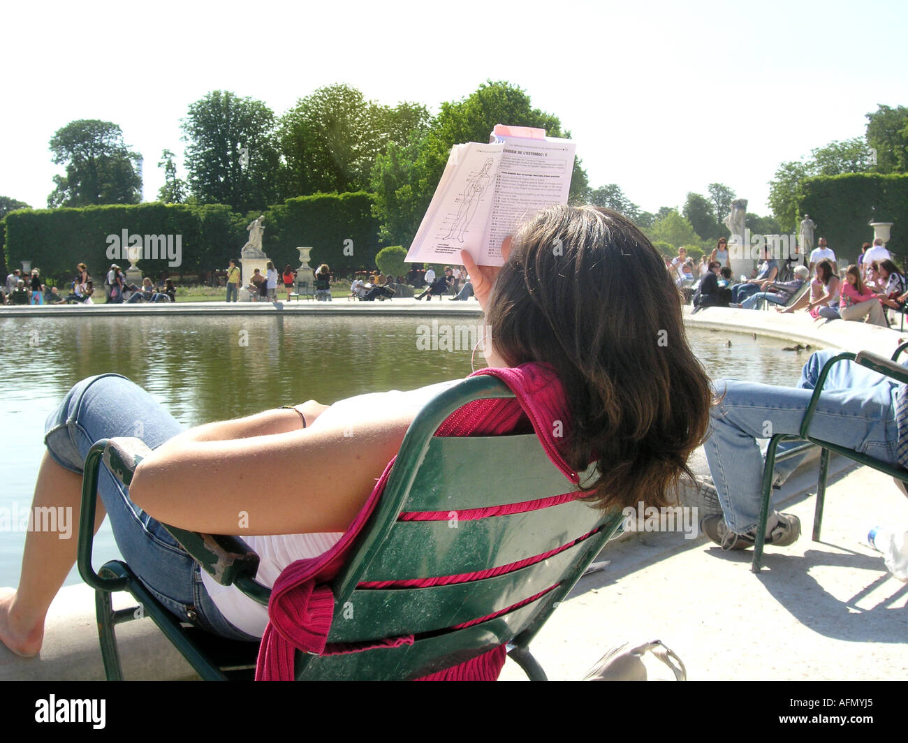 young Caucasian woman reading by round pond in Tuileries Gardens Paris France Stock Photo
