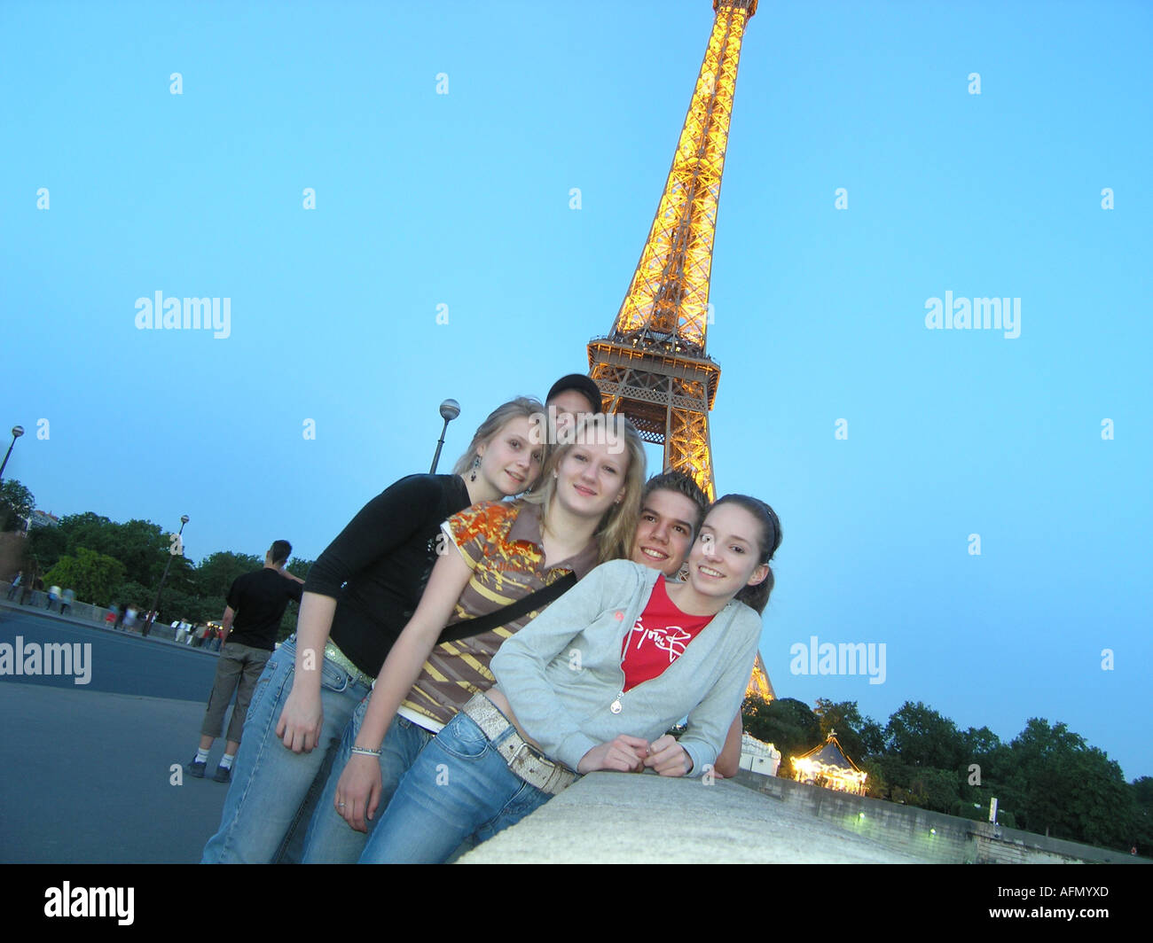 Five students posing on Pont D'iena with Eiffel Tower behind them at dusk  Paris France - Stock Image