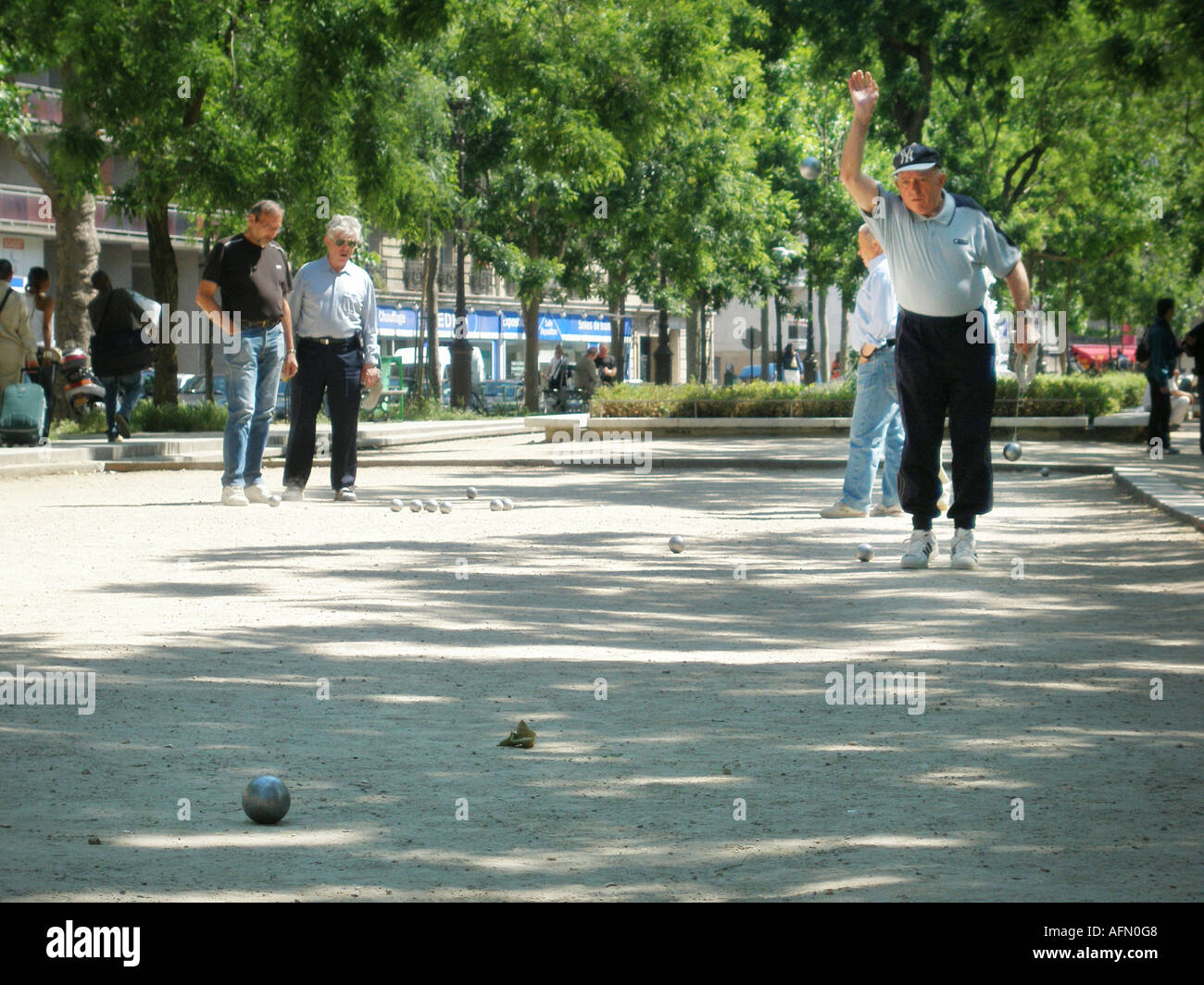 Group of middle aged men playing a game of Petanque in Parisian park Paris France Stock Photo