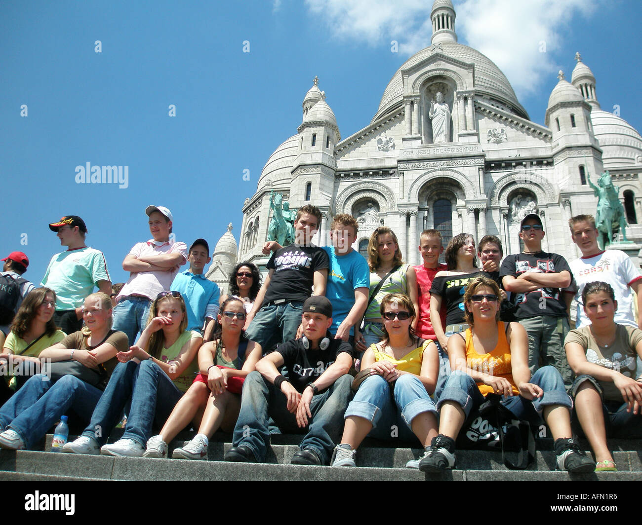 Group of adolescent students sitting on steps in front of Sacre Coeur Montmartre Paris France - Stock Image