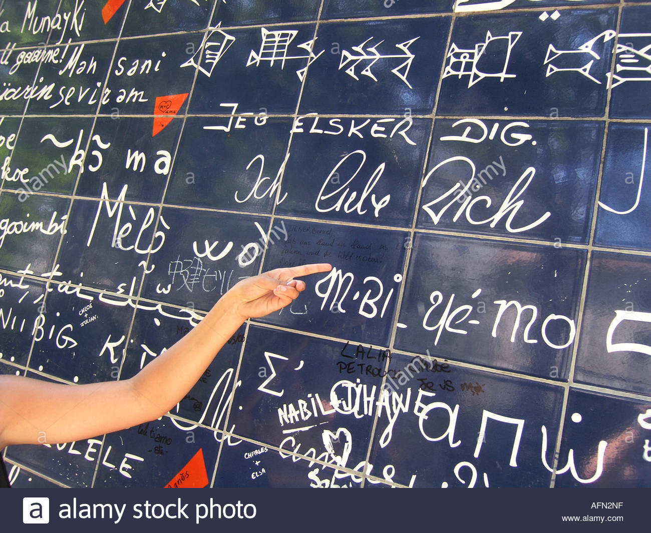 hand pointing at German text 'Ich liebe dich' on Parisian Love wall Place des Abbesses Paris France - Stock Image