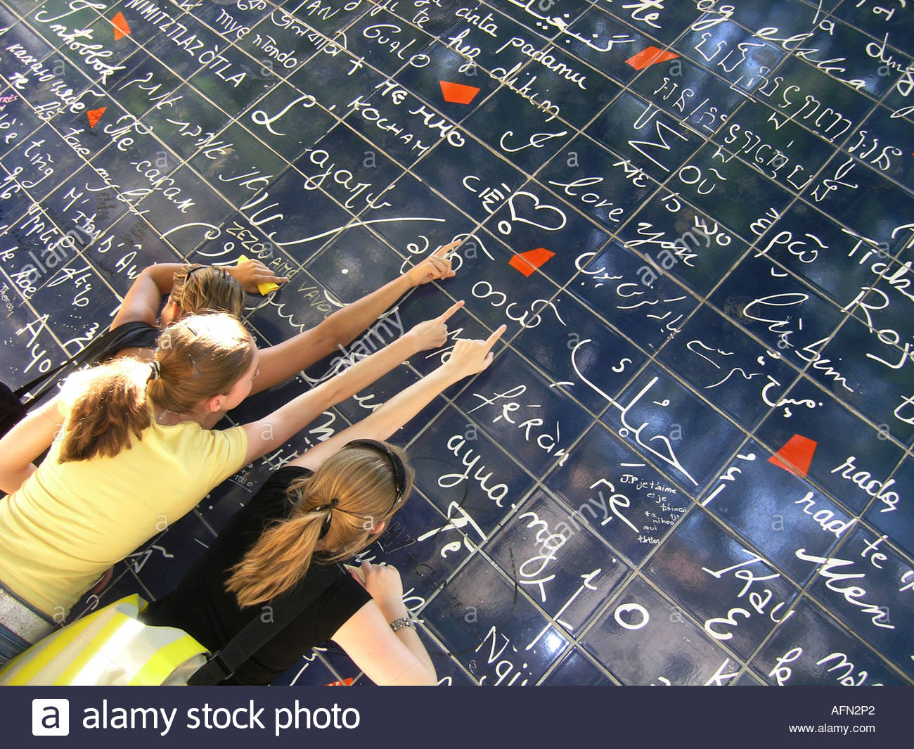 adolescent teenagers pointing at text 'I love you' on Parisian Love wall Place des Abbesses Paris France - Stock Image