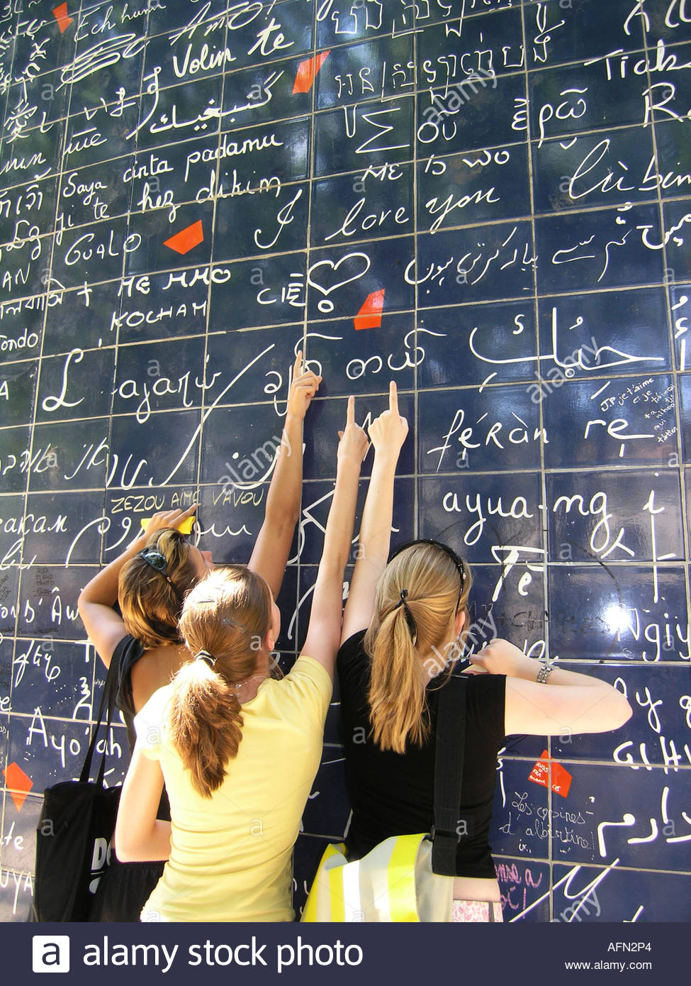 three adolescent teenagers pointing at text 'I love you' on Parisian Love wall Place des Abbesses Paris France - Stock Image