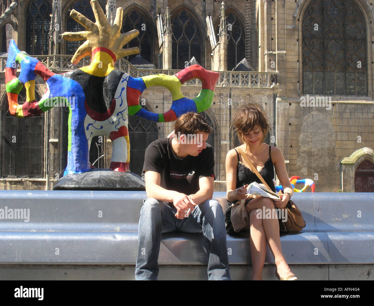 Couple looking on map of Paris at colourful Tinguely fountain at Place Igor Stravinsky Paris France Stock Photo