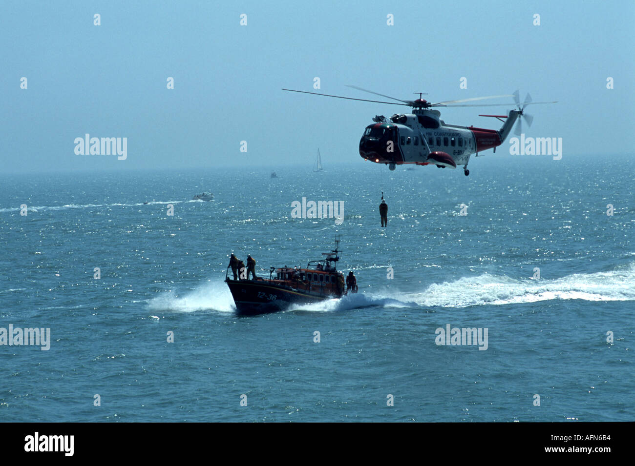 Search and rescue helicopter with man on winch - Stock Image