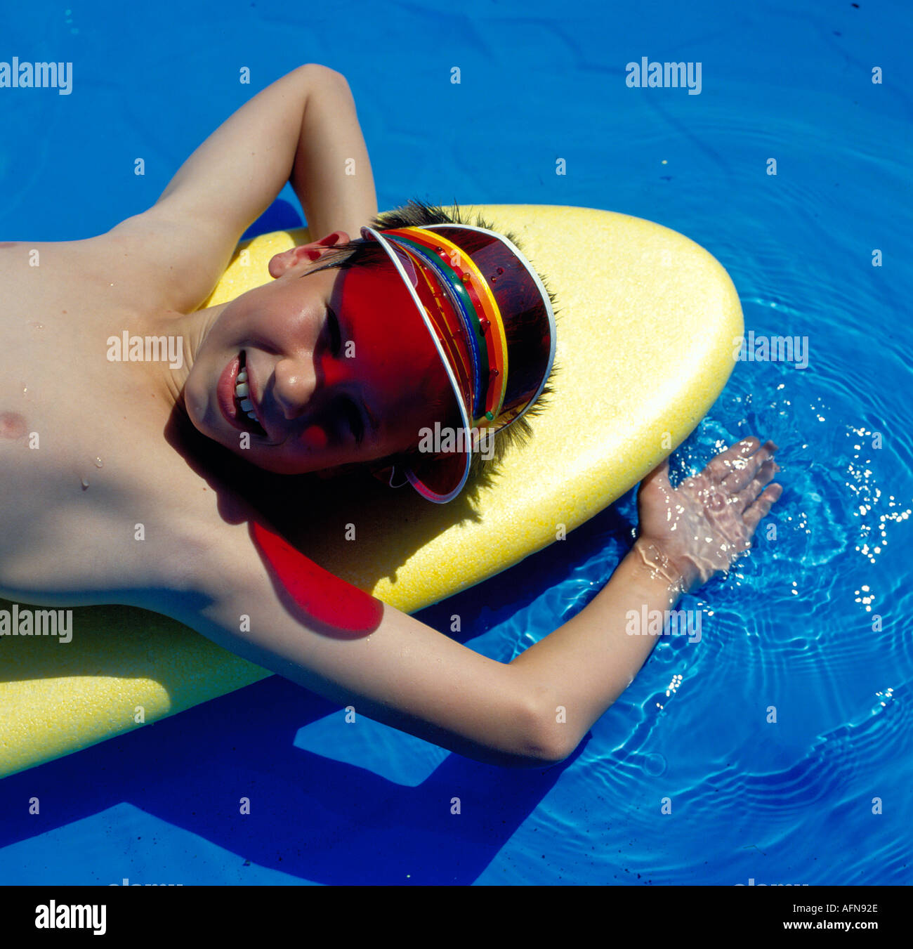 caucasian preteen boy enjoys floating on surfboard in outdoor pool. Photo by Willy Matheisl - Stock Image