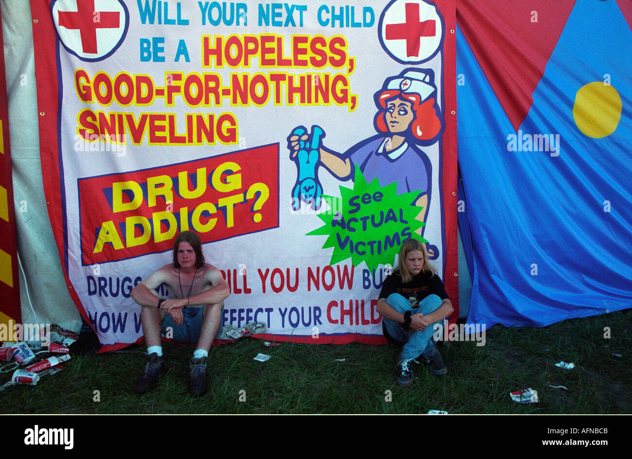 Generation X concert goers sit under a sarcastic banner during Lollapalooza in Kansas City during 1996 cynical genx sarcastic humor, - Stock Image