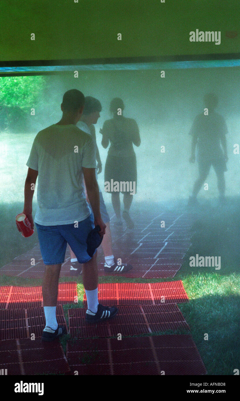 Lollapalooza concert goers walk through a mist room cool cooling summer, - Stock Image