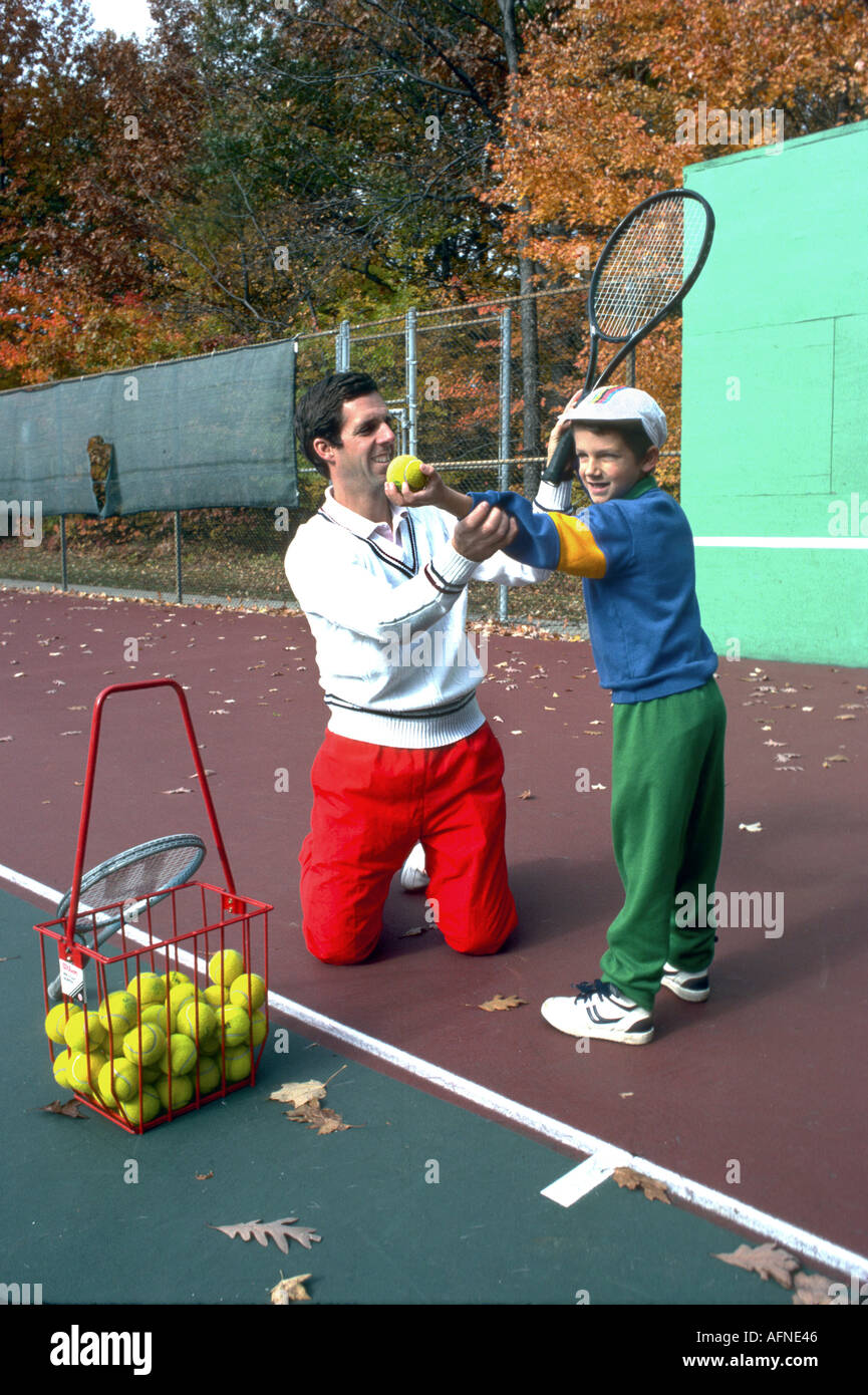 Professional tennis player father teaches son to play tennis Stock Photo