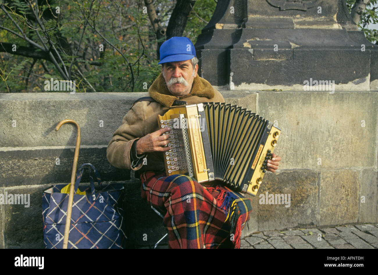 An accordian player serenades passersby on the entrance to the Charles Bridge across the Vltava River in downtown - Stock Image