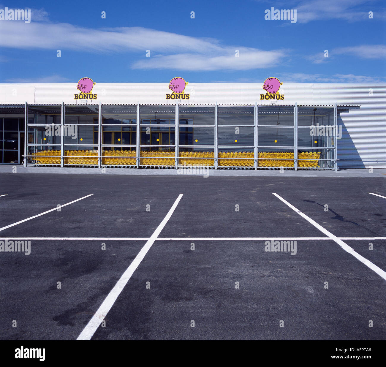 Supermarket car park in Iceland with a row of yellow shopping trolleys - Stock Image