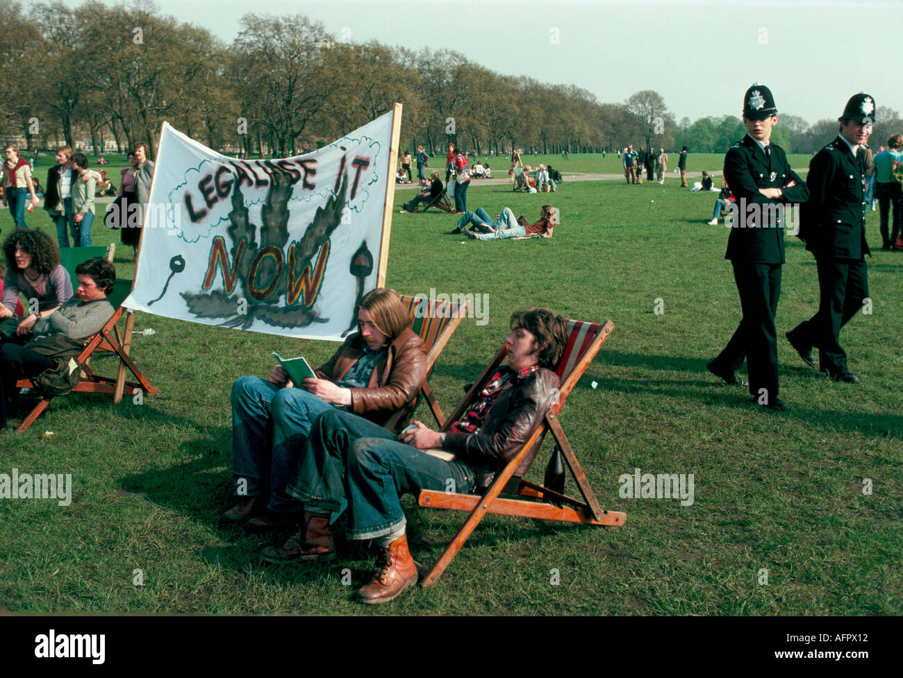 POLICE AND PROTESTERS WITH LARGE BANNER PRONOUNCING LEGALISE IT NOW AT LEGALISE POT DEMO HYDE PARK LONDON 1979 HOMER SYKES - Stock Image