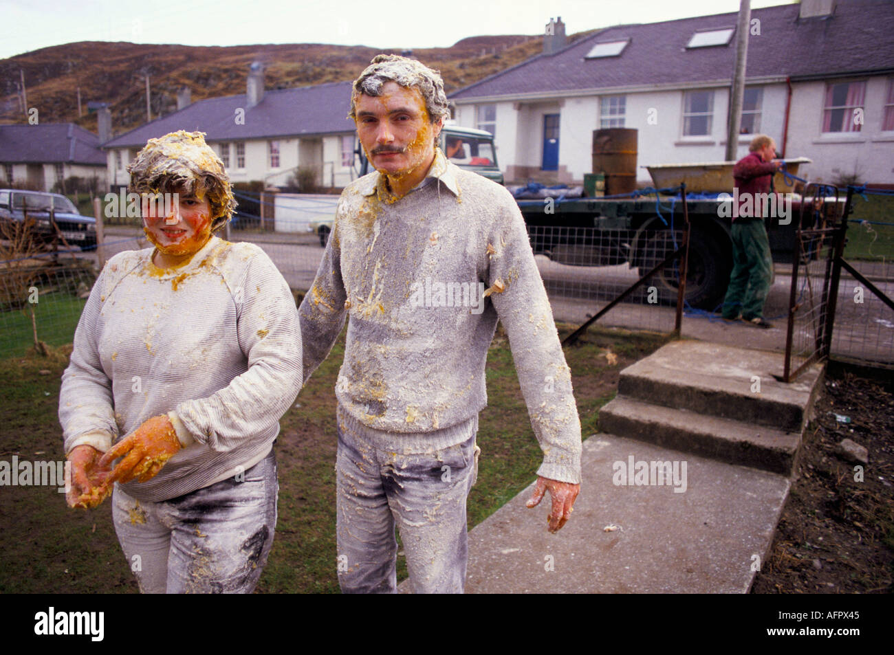 COUPLE DRIVEN THROUGH TOWN COVERED IN EGGS FLOUR PRE WEDDING CUSTOM IN MALLAIG SCOTLAND HOMER SYKES - Stock Image