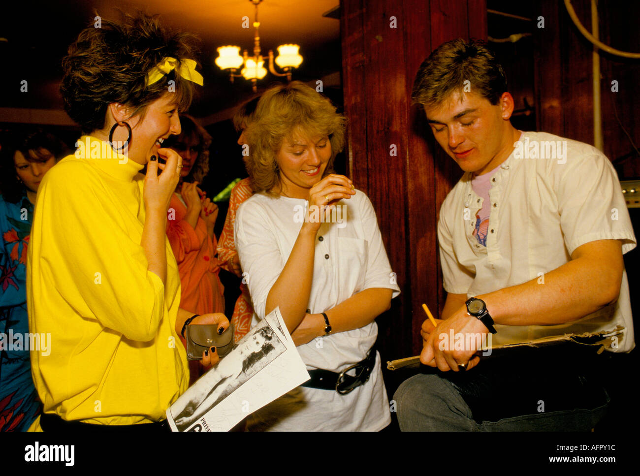 Man signing his autograph for girls after their performance at a hen party London PHOTO HOMER SYKES - Stock Image