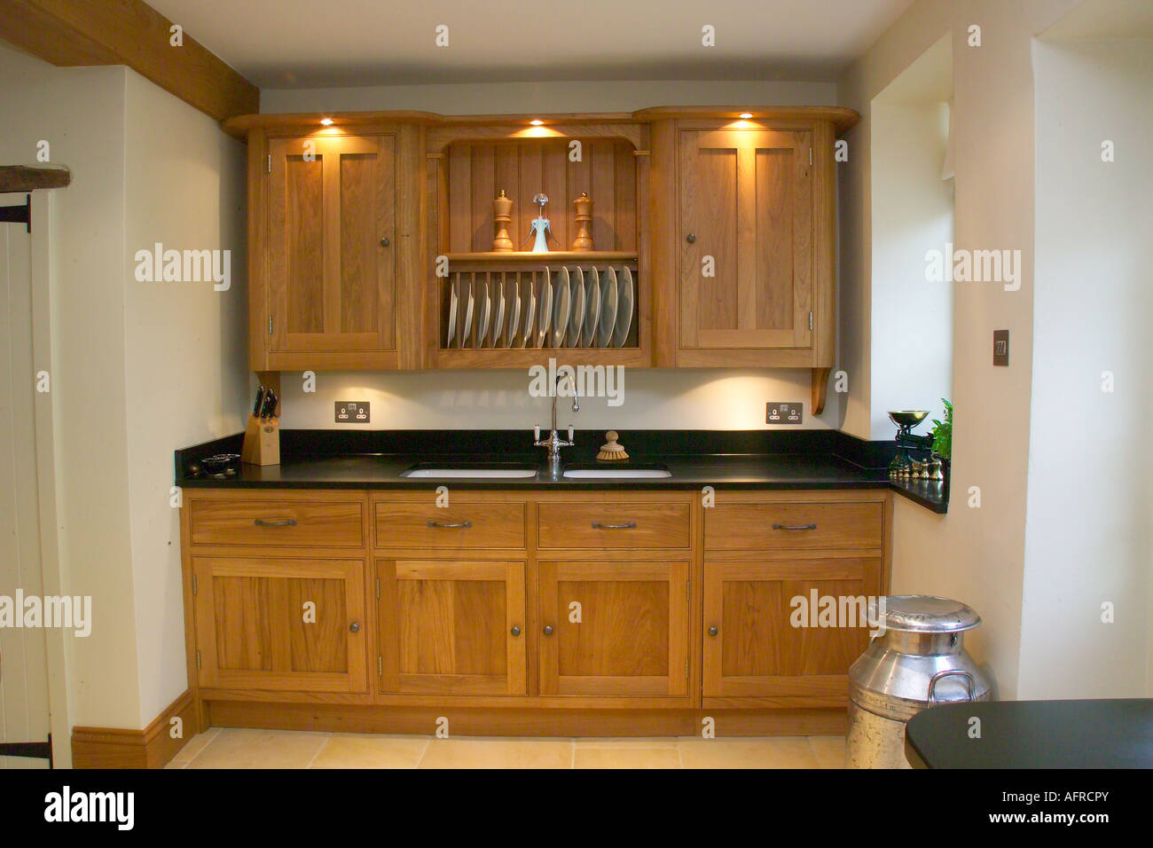 Lighting Above Wooden Kitchen Cupboards With Built In Sink In Modern Kitchen