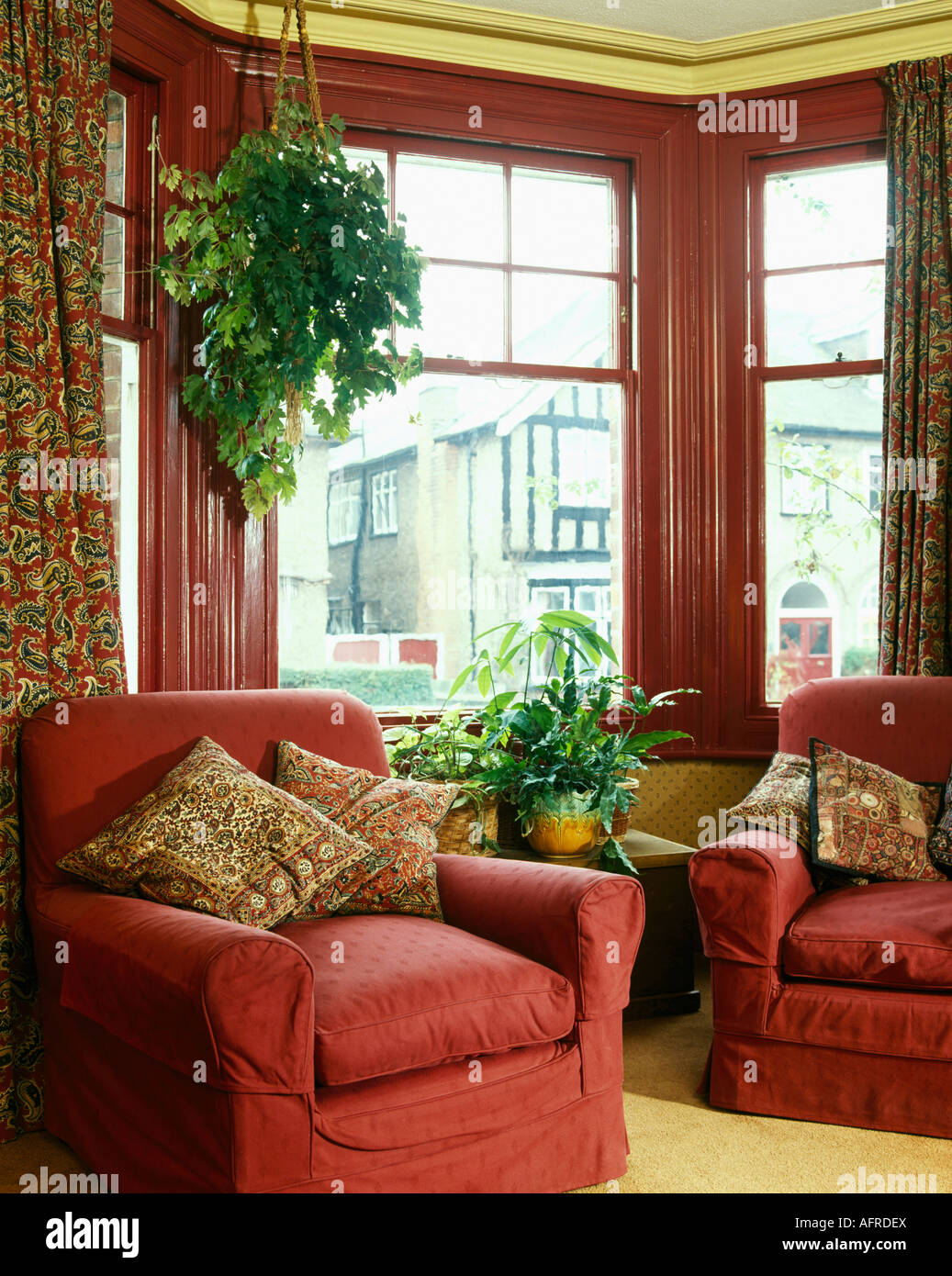 Comfortable Red Armchairs In Front Of Bay Window With Red Painted Frame In  Nineties Living Room With Green Hanging Plants