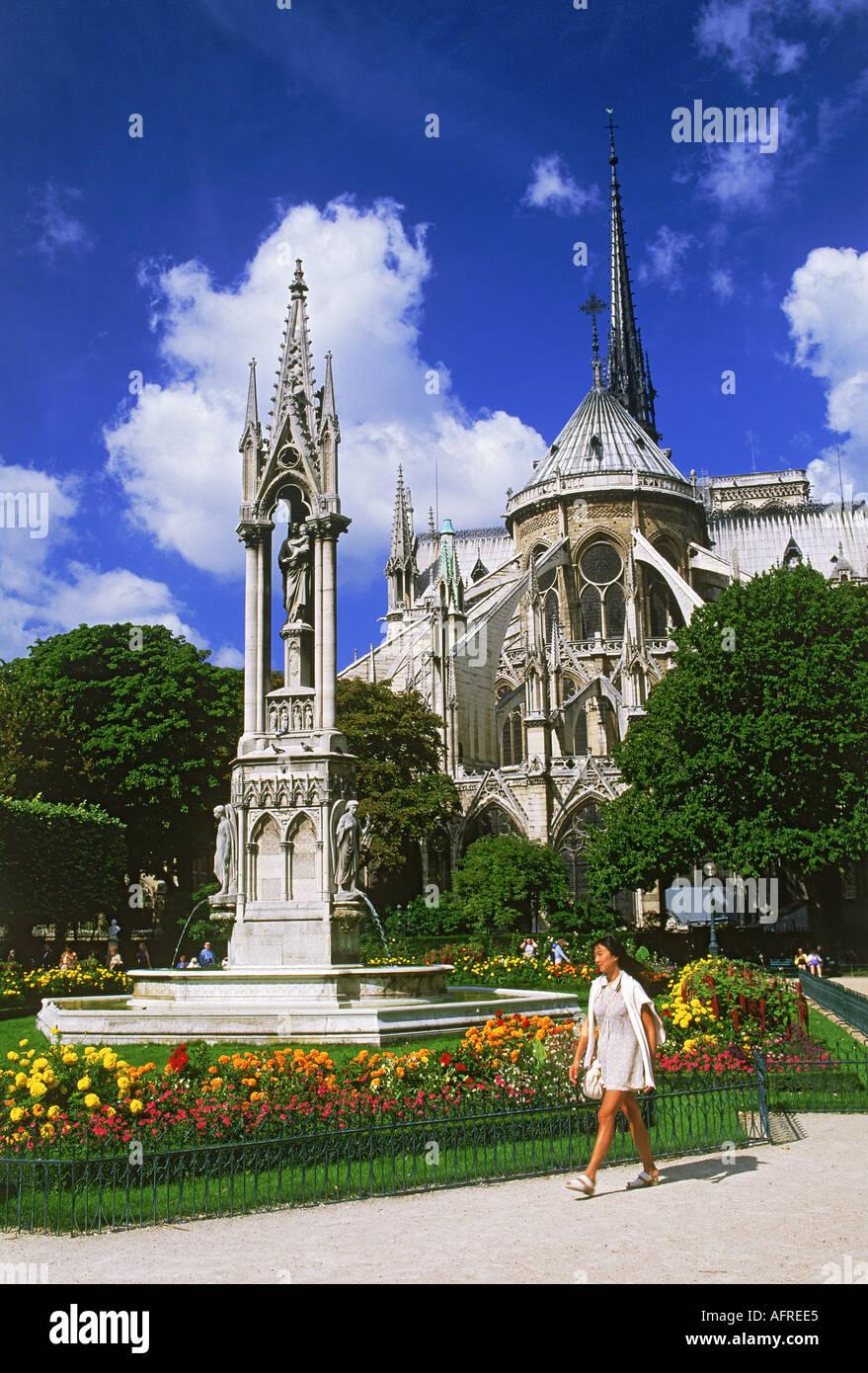 Woman passing gardens on Ile de la Cite with Notre Dame in Paris - Stock Image