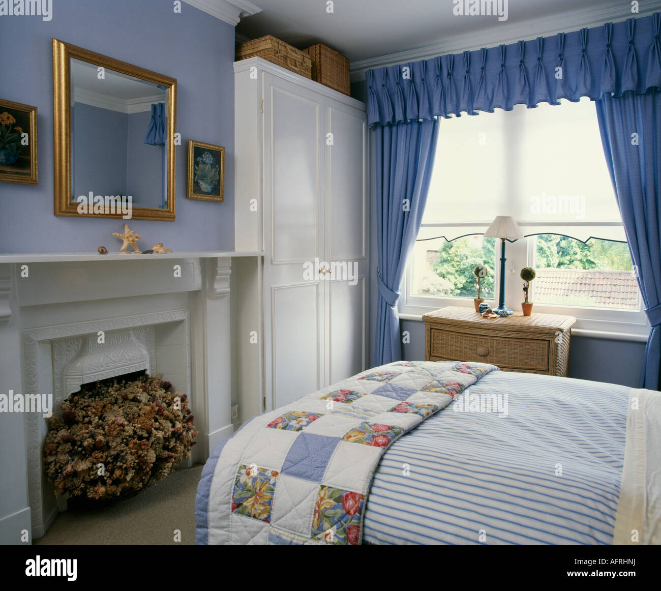 Superior Patchwork Quilt On Bed In Pale Blue Bedroom With White Built In Cupboard  And Blue Curtains