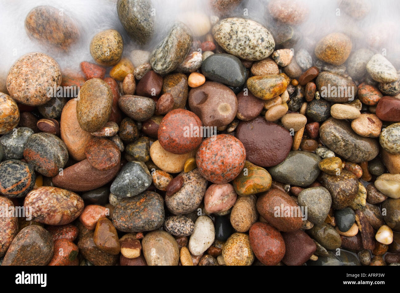 A crashing wave moves over colorful Great Lakes beach rocks on Lake Superior, Michigan - Stock Image