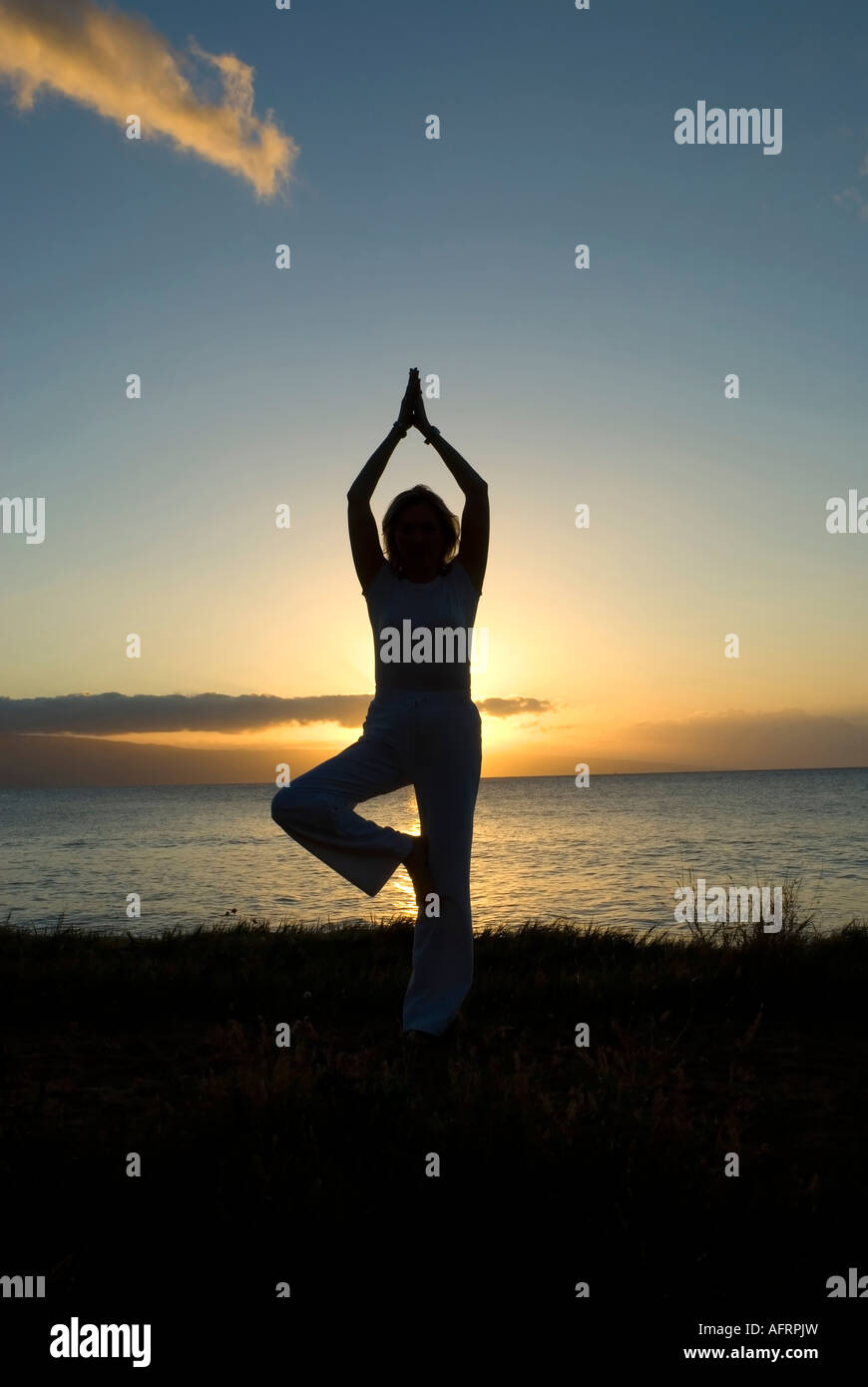 woman in a classic yoga pose at the beach Stock Photo - Alamy