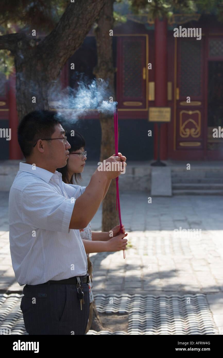 People burning incense sticks and praying, Lama Temple (Yonghe Gong), Beijing, China. - Stock Image