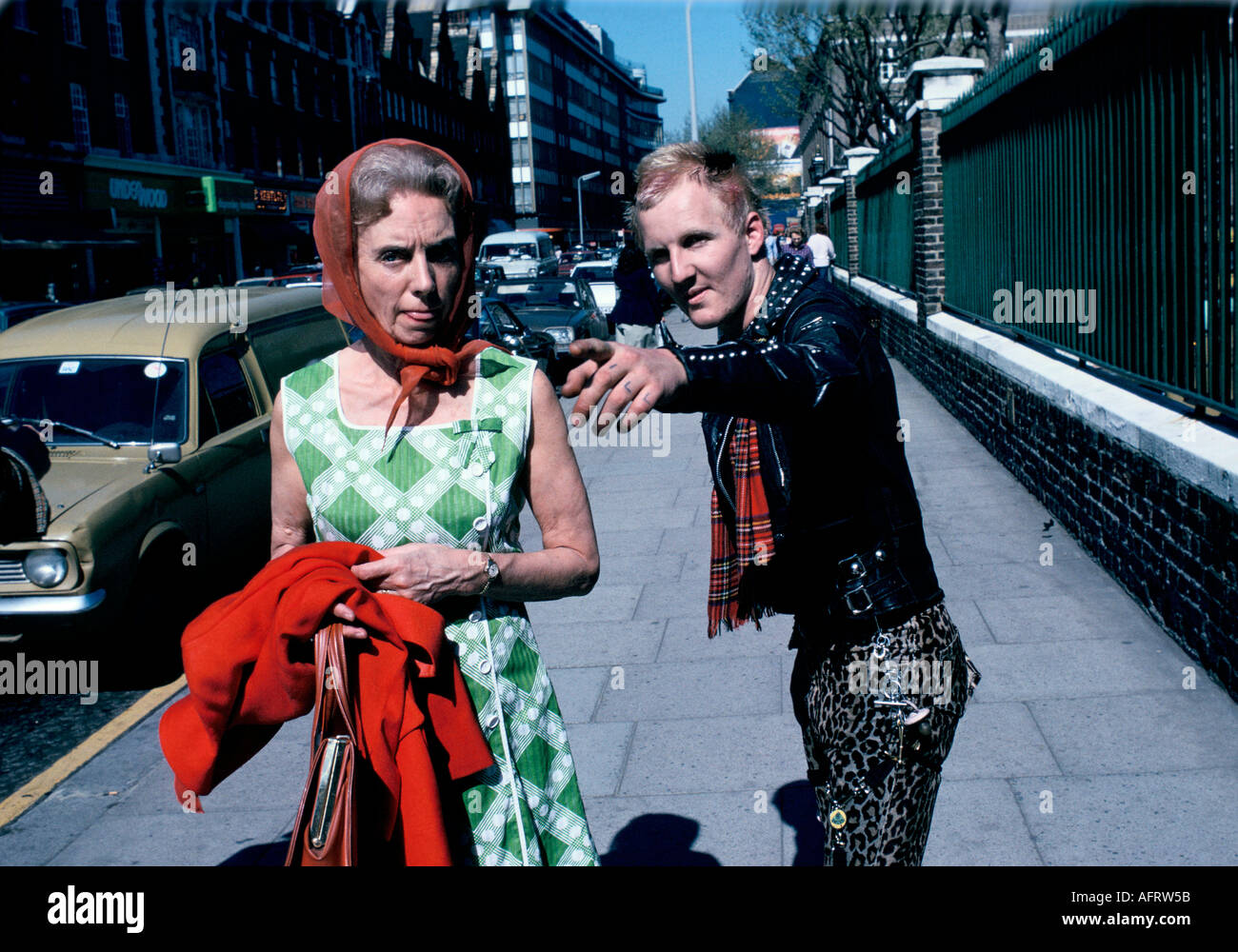 Punk helping passer by on Kings road Chelsea London circa 1975. woman sticking tongue out at photographer 1970s - Stock Image