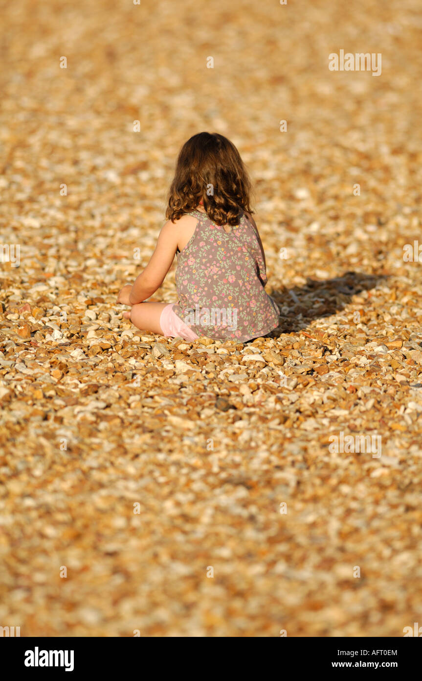 a small young child girl sitting alone on a shingle beach with her back to the camera casting a shaddow - Stock Image