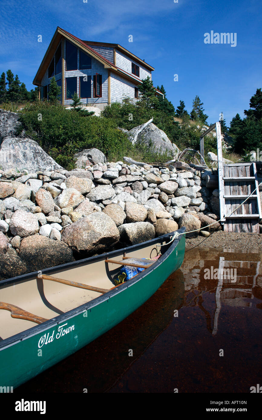 alternative designed waterfront house,moored Old Town canoe