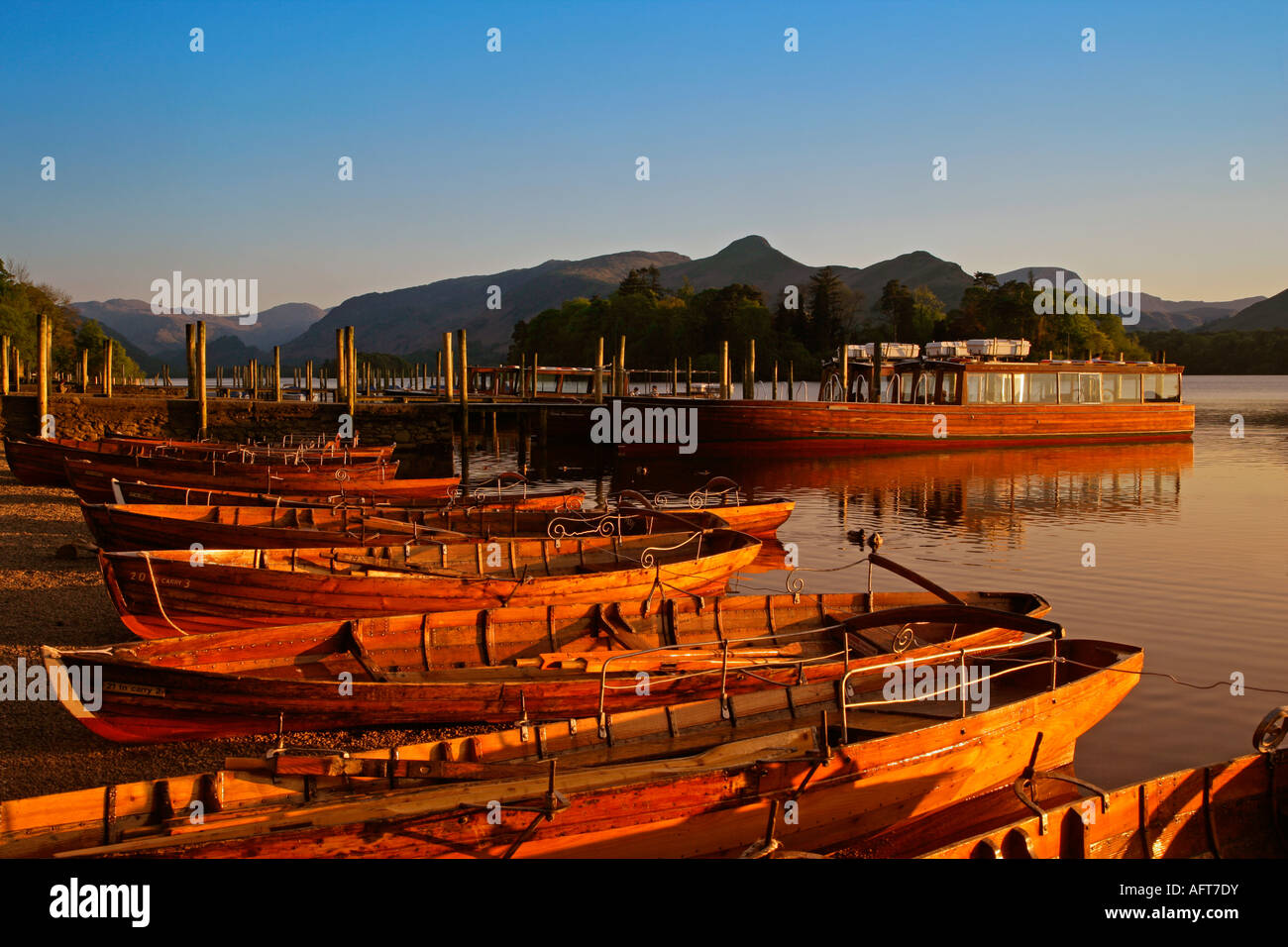 View over rowing boats & cruiser on Lake Derwentwater towards Cat Bells in late evening light Stock Photo