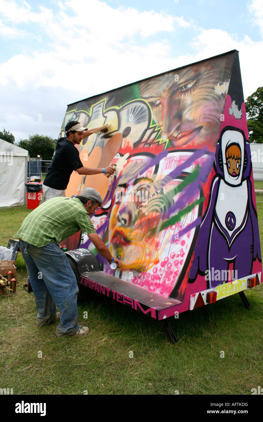two men spray painting on mobile graffiti wall at music festival