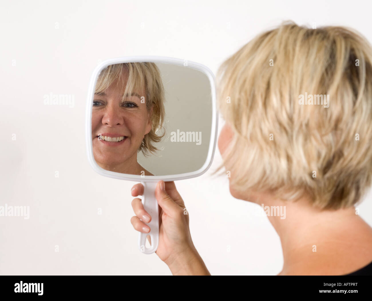 Mature woman holding hand mirror smiling Stock Photo 14019323 Alamy