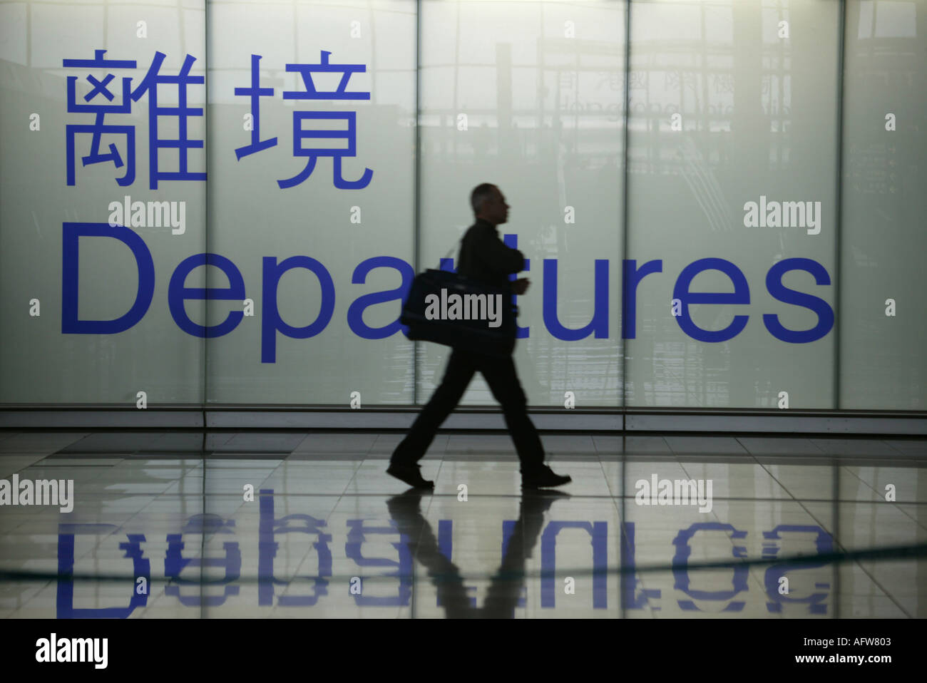 Passenger walks past departure sign at Hong Kongs Chek Lap Kok airport - Stock Image