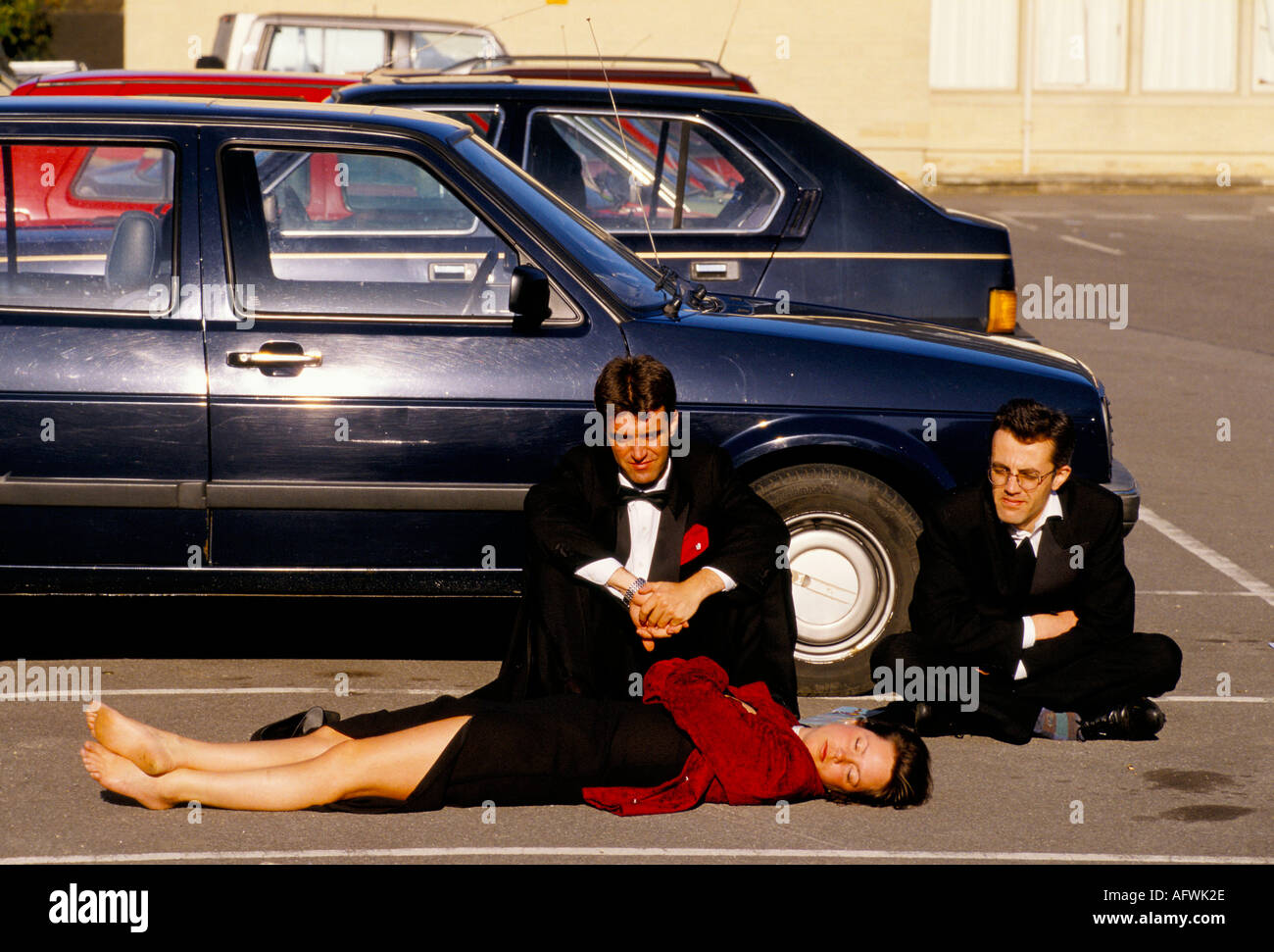 MEN WATCH OVER FEMALE COMPANION LYING ASLEEP CAR PARK AT MAY BALL ROYAL AGRICULTURAL COLLEGE .  1980s UK  HOMER SYKES - Stock Image