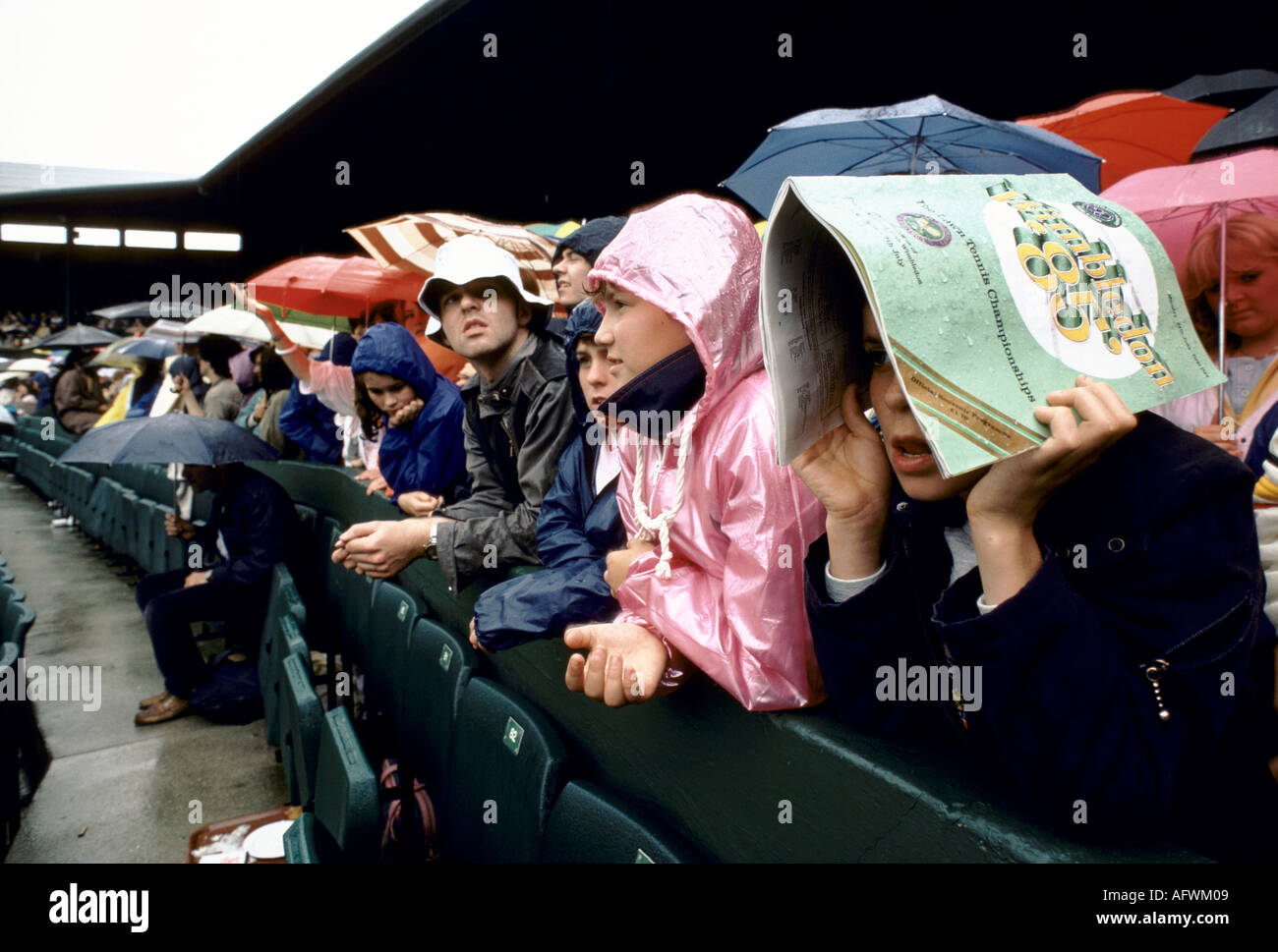 SPECTATORS HOLDING UMBRELLAS MAN USING PROGRAMME SHELTERING FROM RAIN AT THE WIMBLEDON TENNIS CHAMPIONSHIPS HOMER SYKES - Stock Image