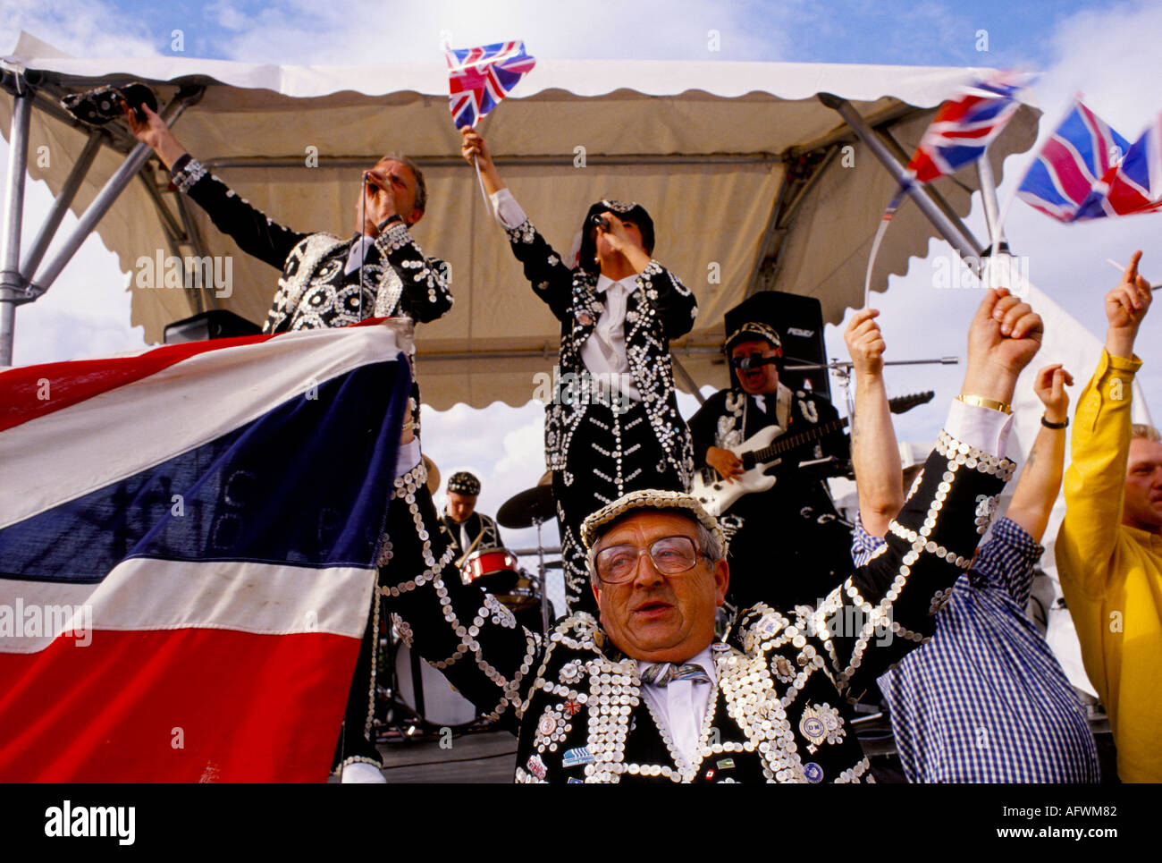 PEARLY KINGS AND QUEENS SINGING  WAVING UNION JACK FLAGS AT THE SURREY  DERBY RACES EPSOM DOWNS. - Stock Image