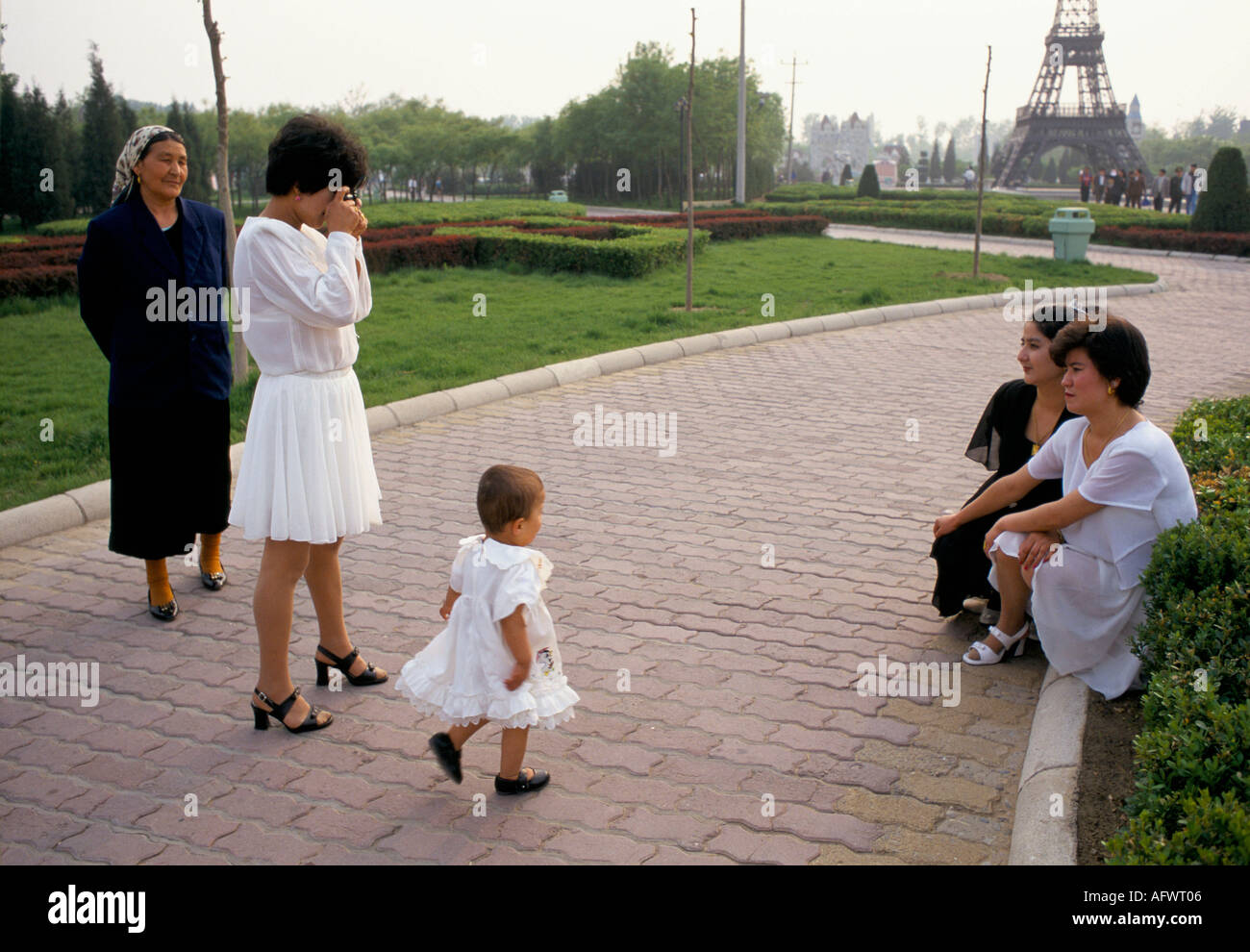 WORLD PARK BEIJING CHINA  TOURIST POSES FOR FAMILY SNAP  SHOTS WITH EIFLE TOWER IN THE  DISTANCE - Stock Image