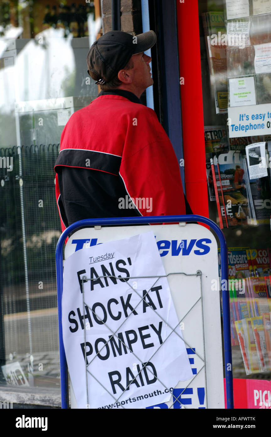 a man in front of fans shock at pompey raid sign looking in news agents window portsmouth football club raided - Stock Image