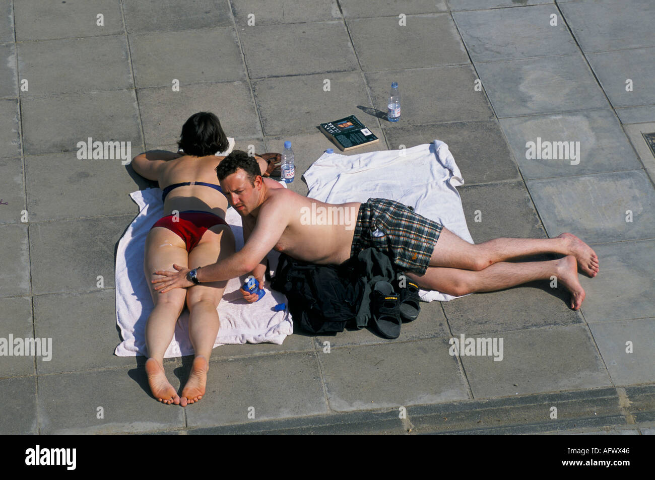 BROCKWELL LIDO MAN APPLYING SUN LOTION TO HIS FRIENDS LEGS ON A HOT SUMMERS AFTERNOON IN SOUTH LONDON - Stock Image