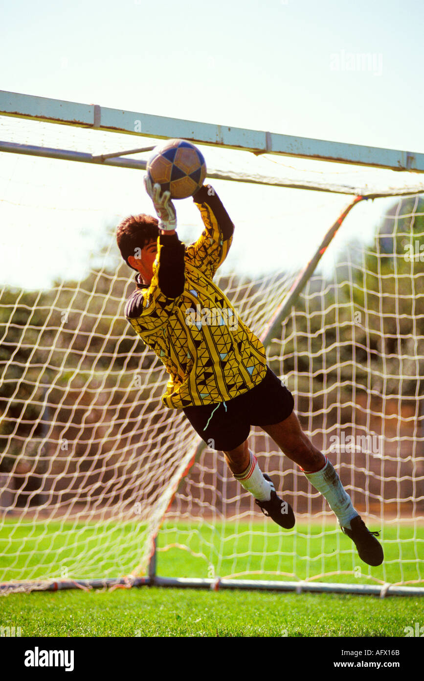 A soccer football goalie leaps to make a save - Stock Image