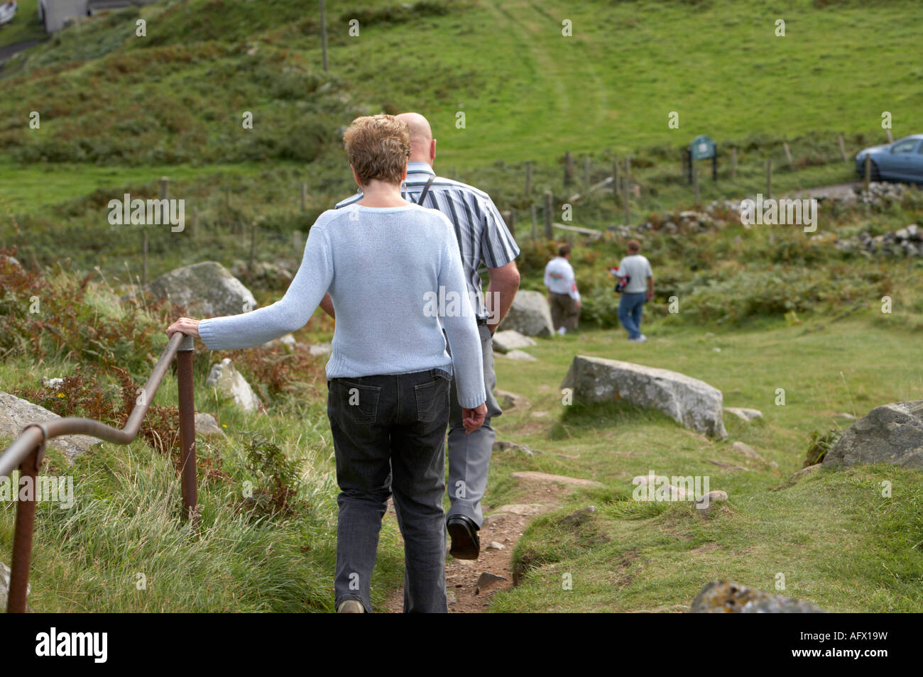tourists walking down badly maintained pathway from top of torr head to car park - Stock Image