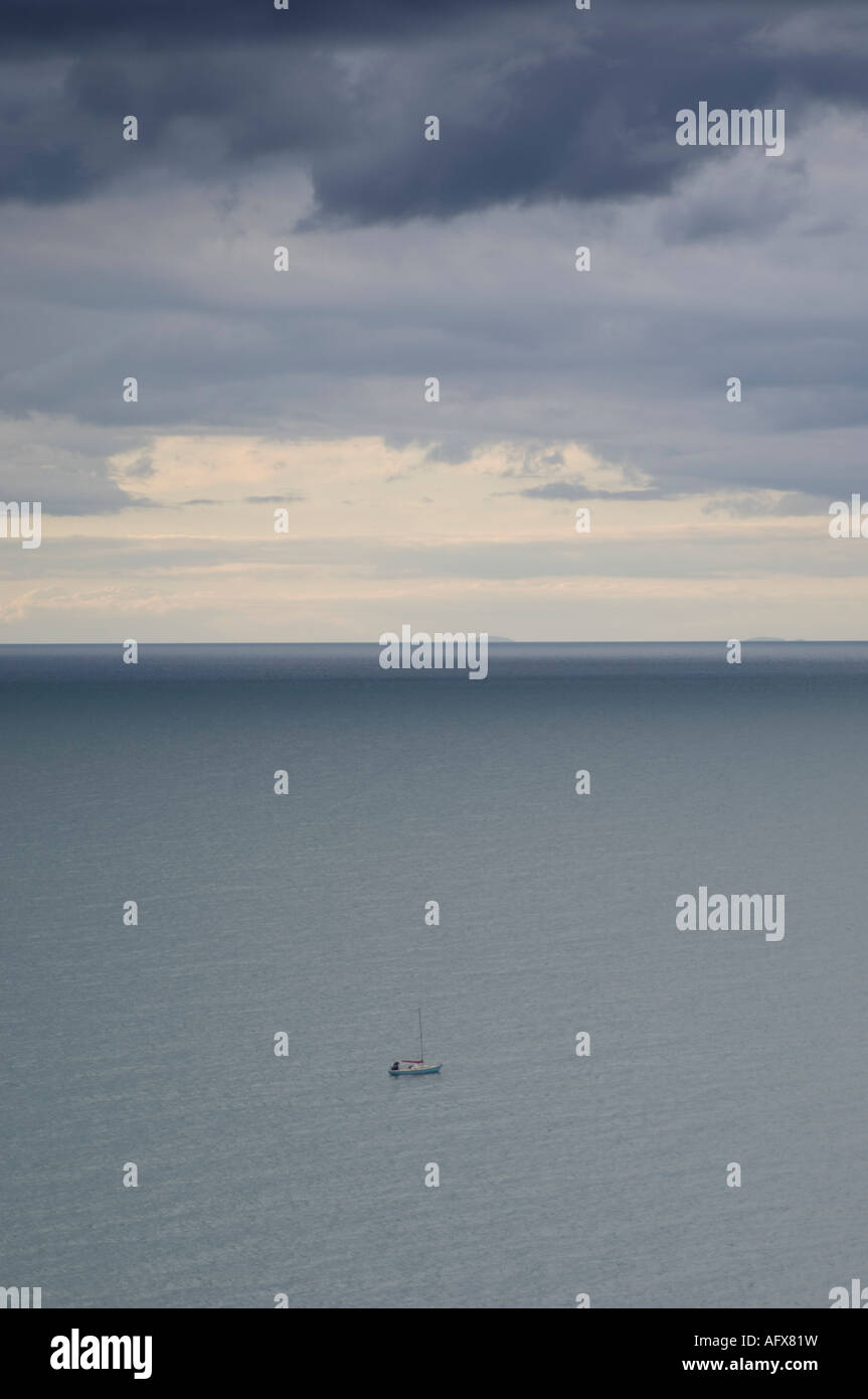 yacht alone in calm sea Cardigan Bay Wales, blue grey sky and empty ocean - Stock Image