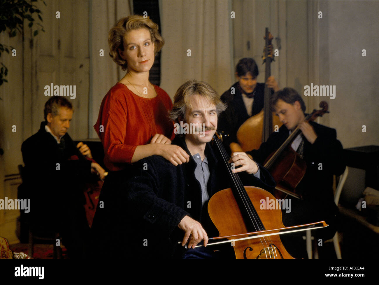 Alan Rickman British actor playing cello Juliet Stevenson British actress on film set of Truly Madly Deeply. 1991 - Stock Image